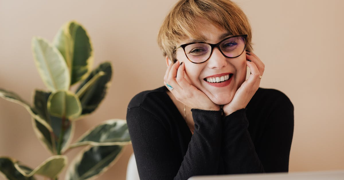 A person wearing glasses and smiling at the camera
