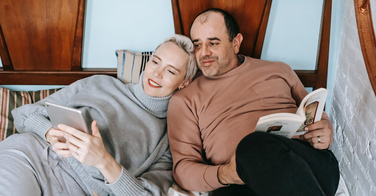 A man and a woman sitting on a bed